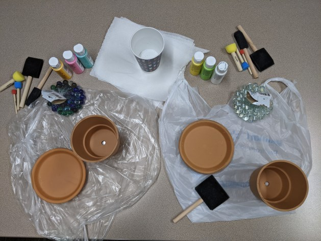 All the things you need to make a bee bath: pots with trays, paint brushes, paint, marbles, and an area to paint.