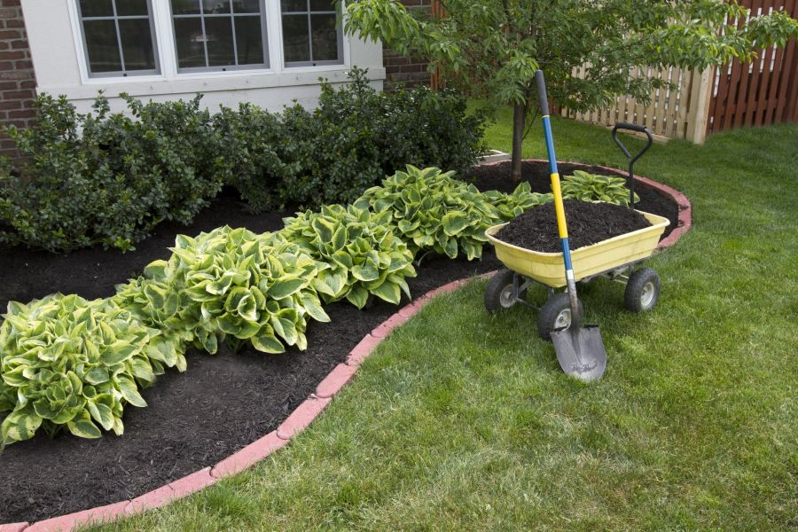 Landscaping outside of a home with a wheelbarrow and shovel.