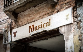 Dilapidated sign for Musical with an arrow