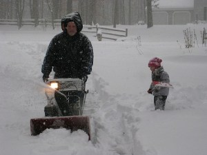 Man snowblowing a driveway in a heavy snowfall while a young boy shovels show nearby