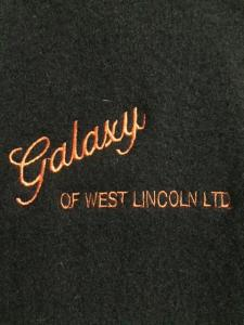 Close-up of the embroidered company name in orange on the front of a black wool jacket