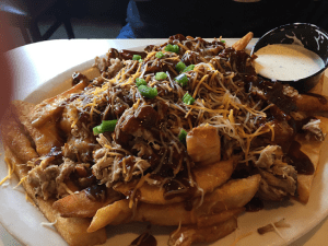huge plate of fries smothered in BBQ rib meat with shredded cheese, chopped onions and lots of BBQ sauce