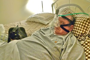 An older man lies in bed wearing a CPAP machine, looking frightened at the camera while his grey cat lays at his side looking at him warily