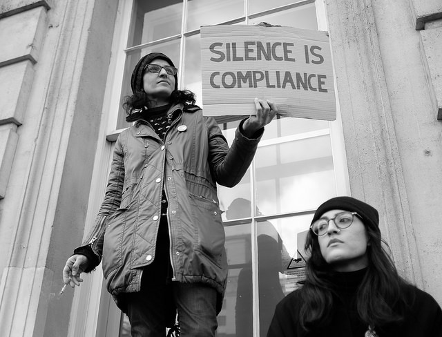 two women outside the US consulate in London England. One holds a sign that reads Silence is Compliance