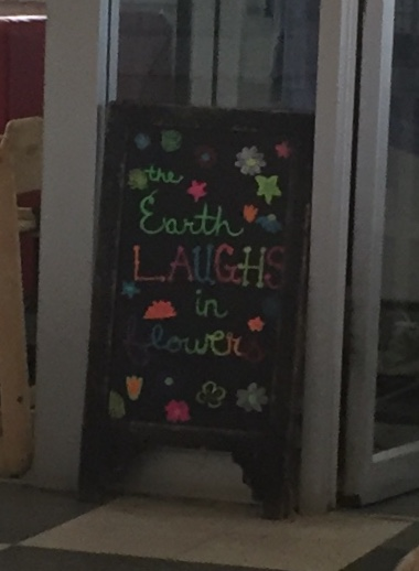 Sandwich board sign reads The earth laughs in flowers.