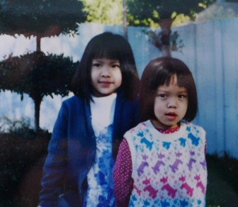 My sister Vy, in blue, and me in red, in front of our childhood home in Anaheim.