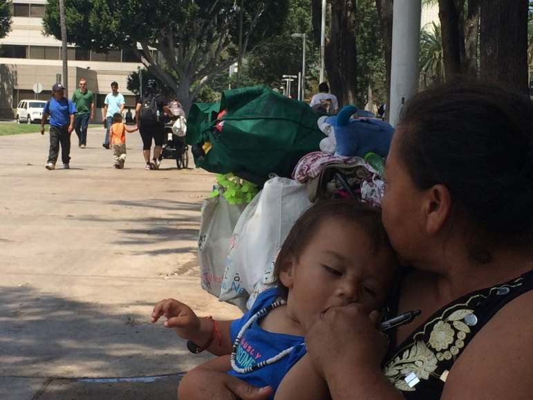 Homeless grandmother Ana Reyes holds her grandson in the county Civic Center this summer.