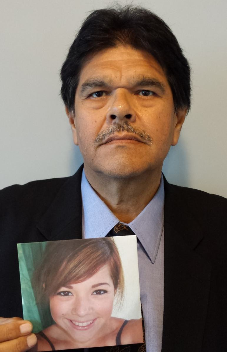 Dr. Olvera holding a photo of his daughter, Emily Rose, who died in 2014.