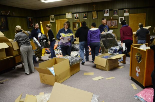 Volunteers sort and carry boxes of new coats at the Knights of Columbus building in Gallup.