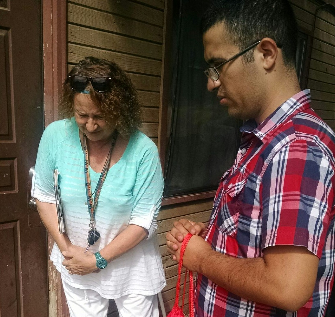 Team members Joanna Klepac and Carlos Lugo pray at a door before knocking.