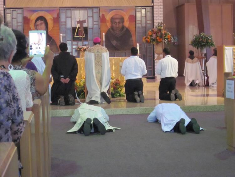 Andres Gallegos, OFM - left - and Jorge Hernandez, OFM, prostrate themselves during Litany of the Saints.