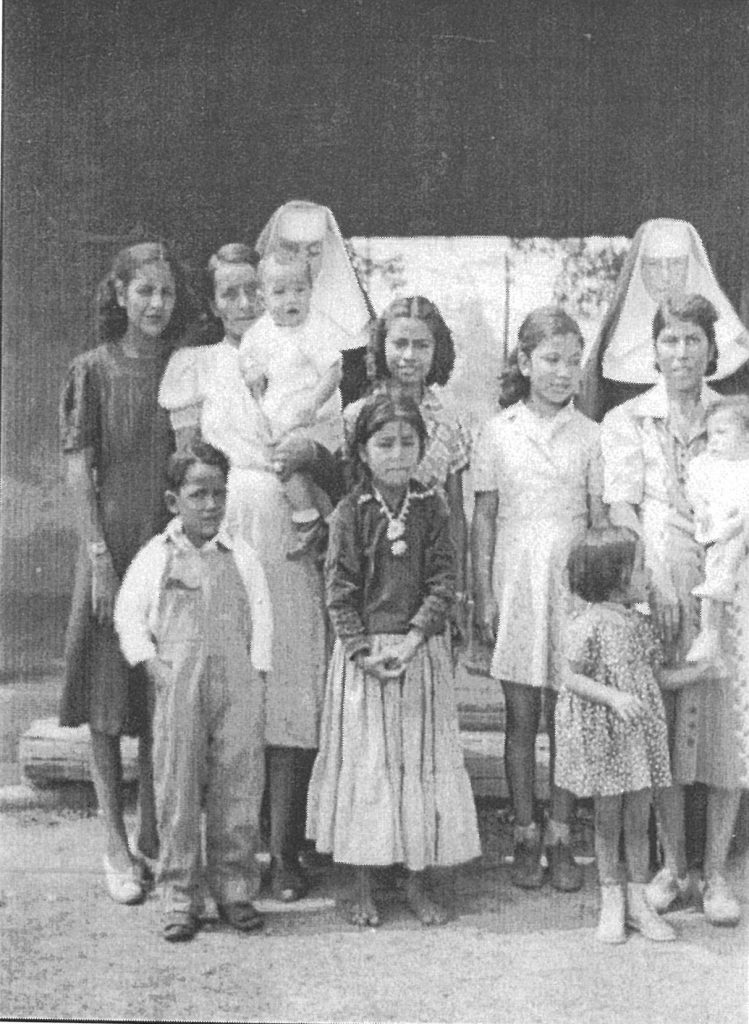 "This was taken at the ""section house"" in Pinta. It shows Sr. Francis on the right in the back. In front of her is Loretto Tso. The Navajo girl in the front is Nellie Yazzie Shirley and in back of her is Stennie Ashley."