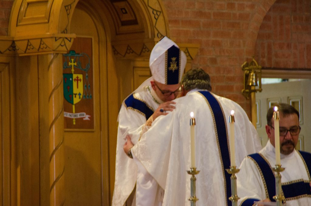 Bishop Wall embraces the newly-ordained priest.