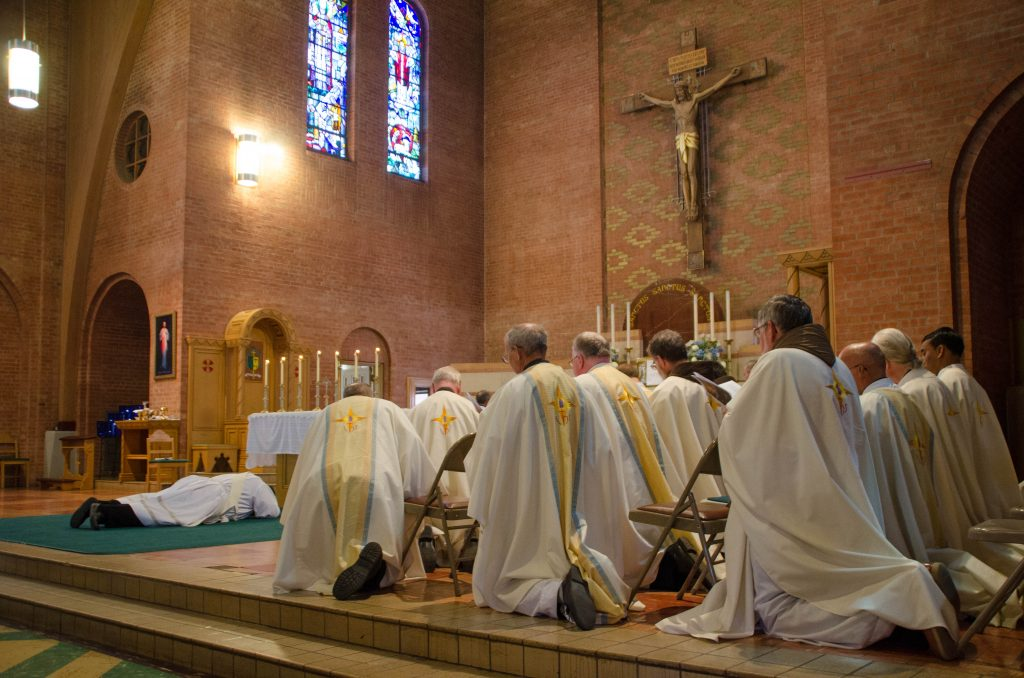 Diocesan priests pray the Litany of Saints as Robert Badger prostrates himself.