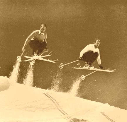 2_skiers_catching_air_on_vintage_skis
