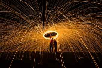 person standing beside another person holding fire poi