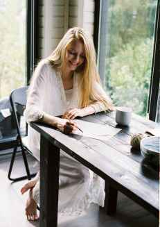 smiling barefooted lady writing thoughts on paper at home