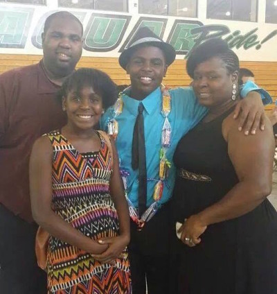 Keshawn Brooks (center) with his family during his middle school graduation.