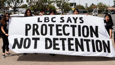 Five women hold up a banner that says L B C says protection not detention.