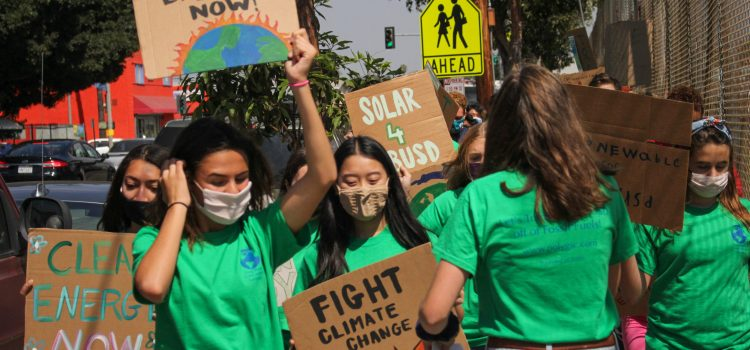 """Students walk together, toward the camera, while holding signs that say """"clean energy now"""" and """"fight climate change."""""""