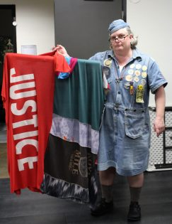 Frau Fiber, founder of Sewing Rebellion, holds up her own poncho body banner that expresses her message of justice during this time of political unease in the country.