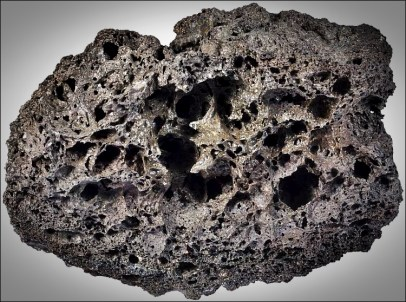 Vesicular texture: Magma typically has some gas in solution. During eruptions, that gas effervesces out of solution, like CO2 bubbling out of a soda. As the magma freezes, these bubbles are preserved as vesicles, and rocks containing them are called vesiclular. Image: Scoria is a highly vesicular volcanic rock. It usually has a basaltic composition, but this is not a defining parameter. It just has to be very porous. Tenerife, Canary Islands. Width of sample is 7 cm. (from sandatlas.org)