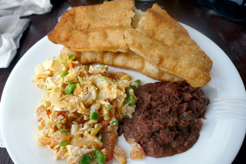 breakfast of scrambled eggs, refried beans and fry jacks