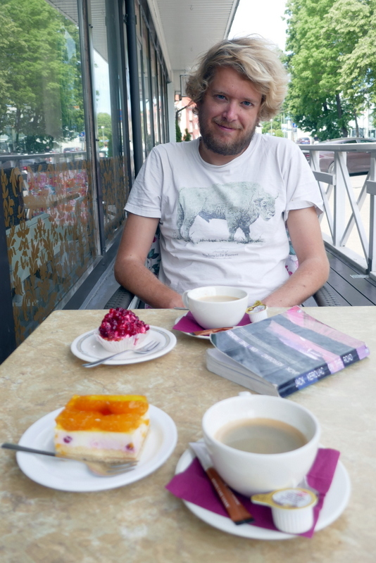 Tom with coffee and cake on the terrace of Wironia Hotell in Jõhvi.