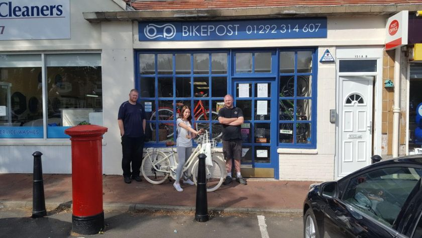 The Bike Post staff posing outside their storefront in Troon with the VOLT Kensington e-bike