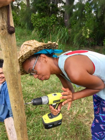 whitney uses a power drill for the first time as part of her Kauai summer internship