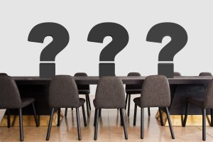 conference table and chairs with three large question marks on the table