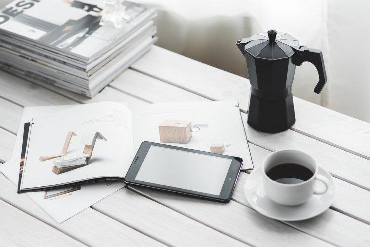A white desk with a stack of magazines next to an open magazine with an iPad resting on it. Next to the iPad is a cup of coffee and a coffee pot