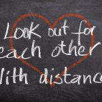 "A black chalkboard with a red heart. The words ""Look out for each other! With distance!"" are written in white over the heart"