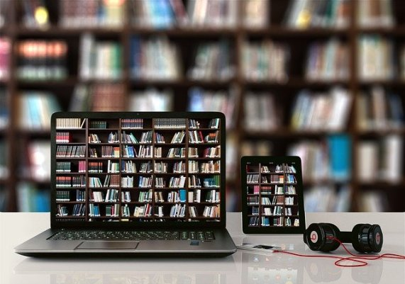 Image is of a laptop and tablet, sitting on a desk next to a set of headphones, plugged into a smart phone. On the laptop and tablet screen is the image of bookshelves. The background is a blurred image of the same bookshelves.