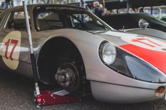 Porsche 904 race car in the pits with a wheel off