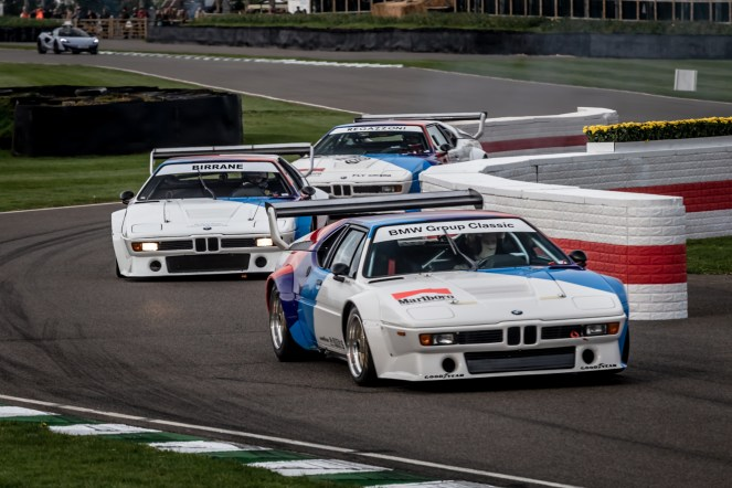 Three BMW race cars racing at Goodwood