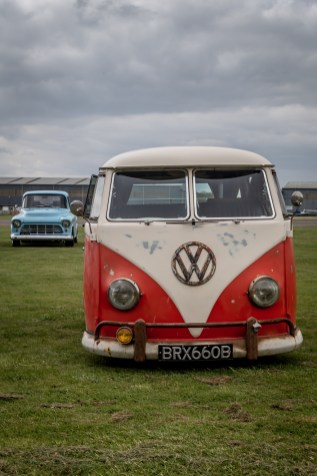 Red and white Volkswagen split screen camper and blue Chevy pick up truck