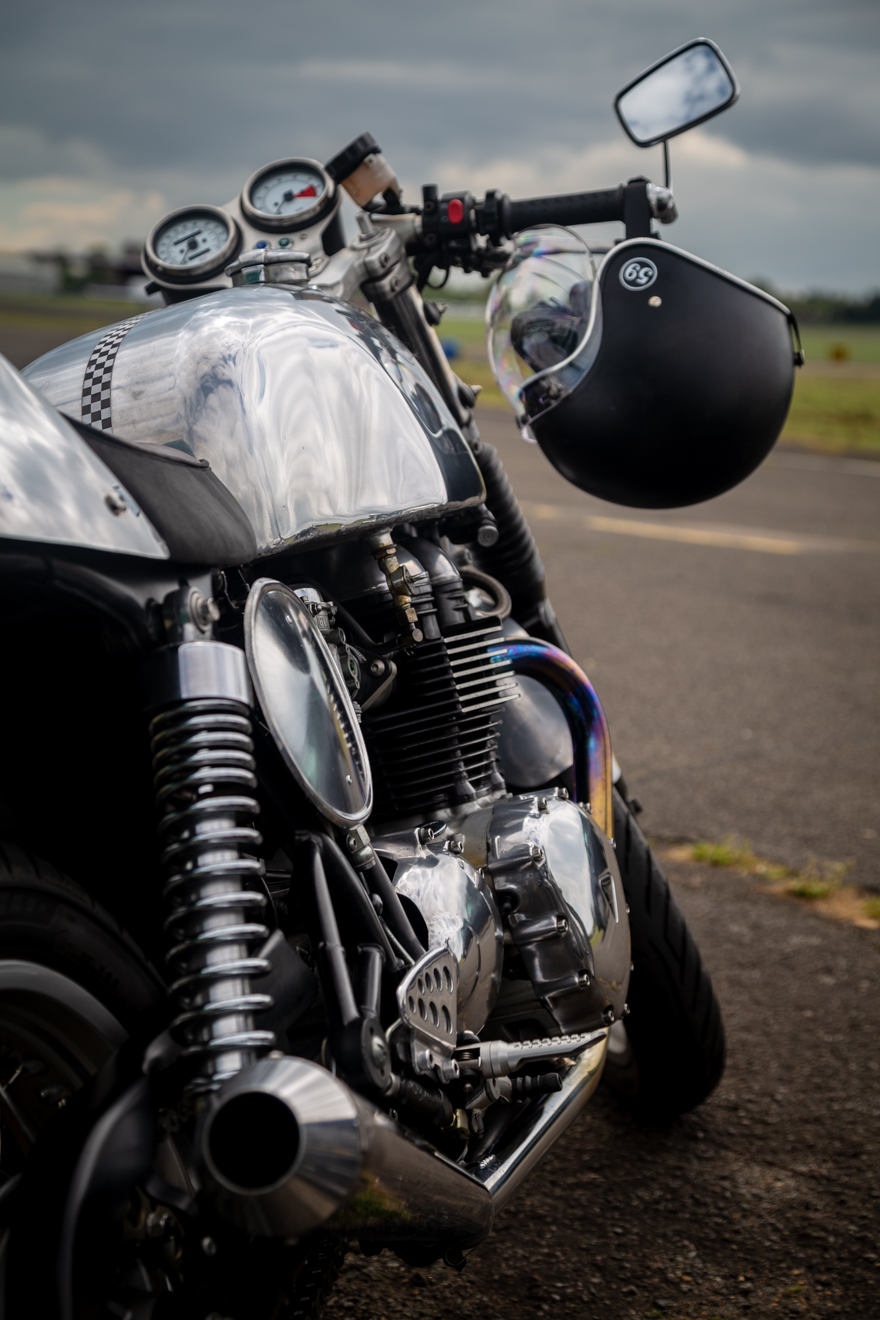 Crash helmet hanging from handlebars of a Triton cafe racer motorcycle