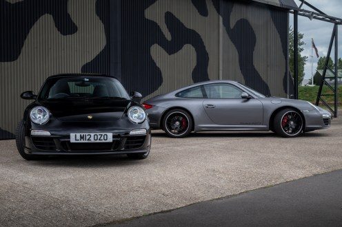 Two Porsche 911's in front of camouflage aircraft hanger