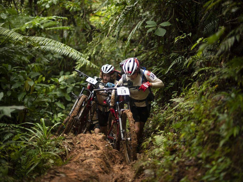 una pareja de ciclistas de montaña luchan por subir una cuesta enlodada en la isla de fiyi