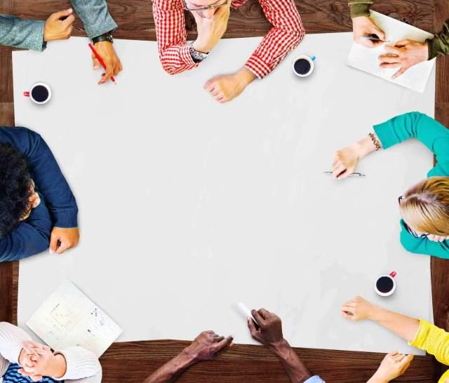 Vooozer ou Voozer? Pessoas apoiadas em uma mesa de trabalho pensando em nome para empresa.
