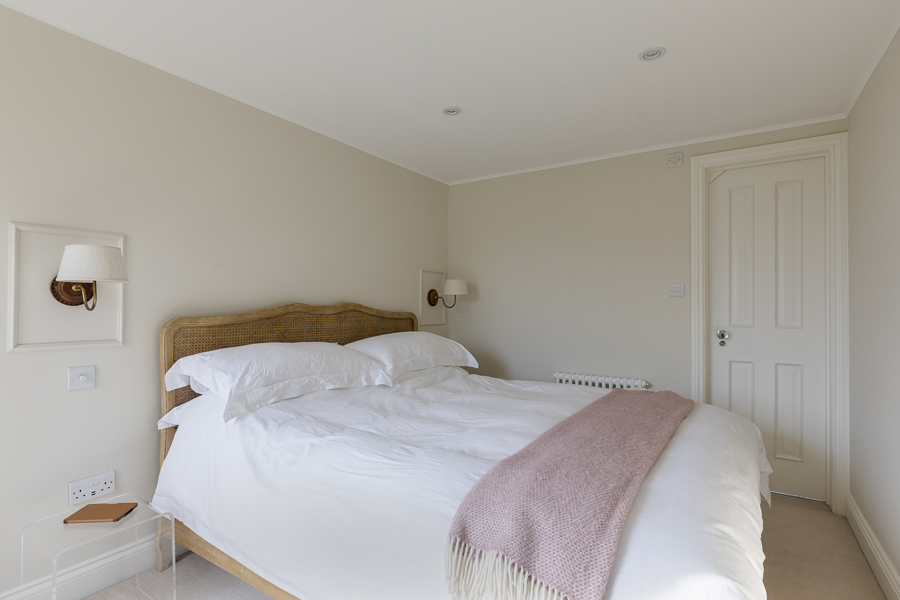 0631 cream bedroom walls double bed with white covers and pink throw