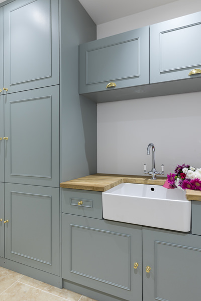 647 shaker green cabinets in utility room with belfast sink and wooden worktop in W4