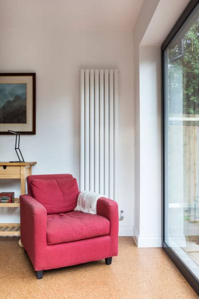 0527 retro interiors living room with tall radiator and red arm chair in North West London