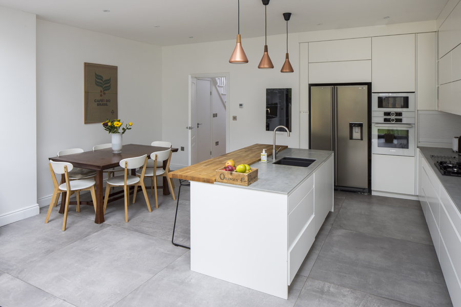 0557 white kitchen with wooden breakfast bar copper island lights and concrete tiles in south wimbledon