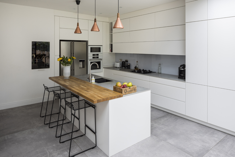 0557 modern white kitchen with wooden breakfast bar copper pendants and concrete tiles in london