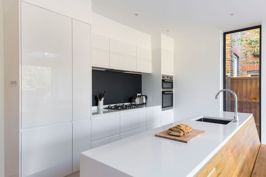 0558 white high gloss Howdens kitchen with dark blue splashback