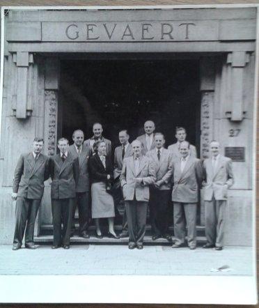 Nic van Baarle (zesde van rechts) voor een gebouw van Gevaert film. Collectie erven Van Baarle