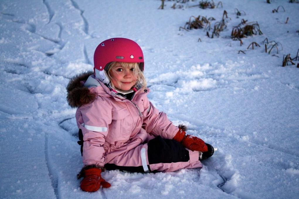 Девочка в шлеме сидит на льду