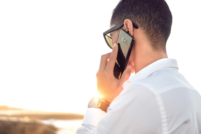 Homme de dos qui téléphone à ses anciens clients